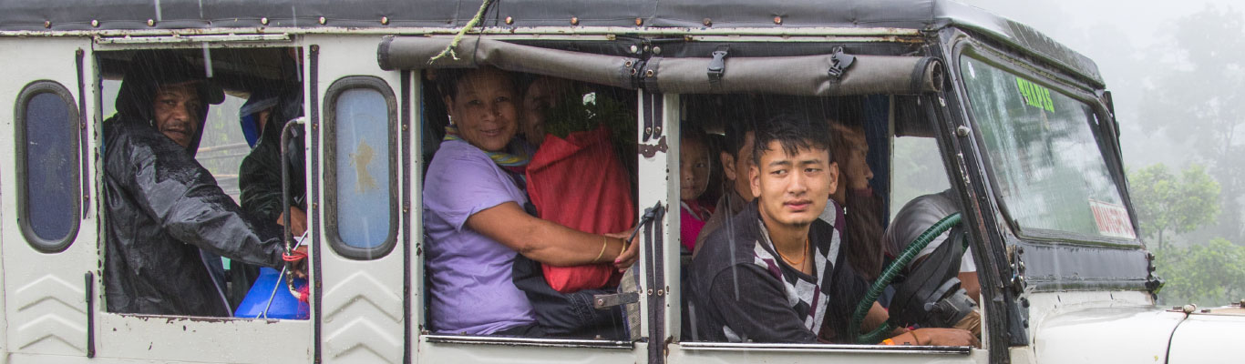 Local travel by crowded jeep on a rainy day